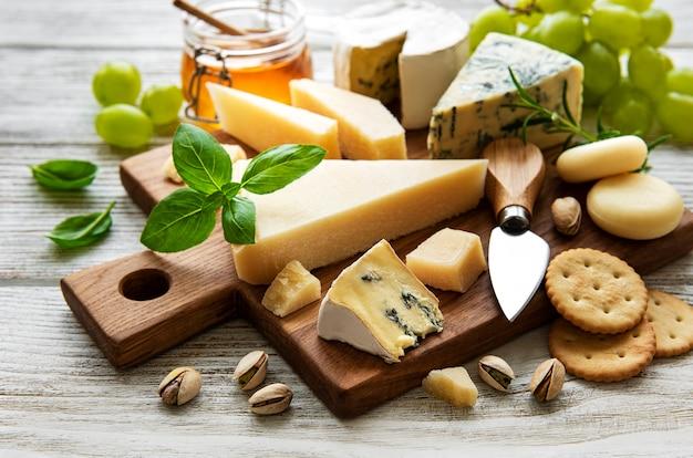 Verschiedene käsesorten auf einem weißen holztisch