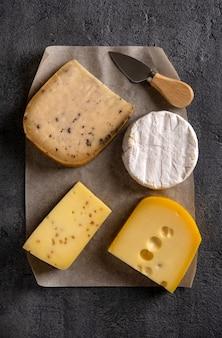 Verschiedene käsesorten auf grauem brett. dunkel launisch. draufsicht. nahansicht.