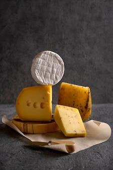 Verschiedene käsesorten auf grauem brett. dunkel launisch. freier speicherplatz für ihren text. nahansicht.