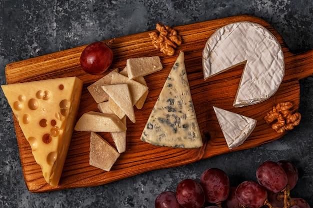 Verschiedene käsesorten auf holzbrett