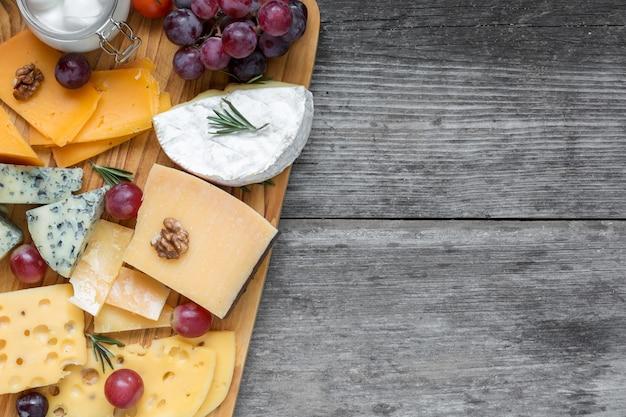 Verschiedene käsesorten auf holzbrettplatte serviert mit walnüssen, trauben und rosmarin auf rustikalem holzhintergrund, draufsicht