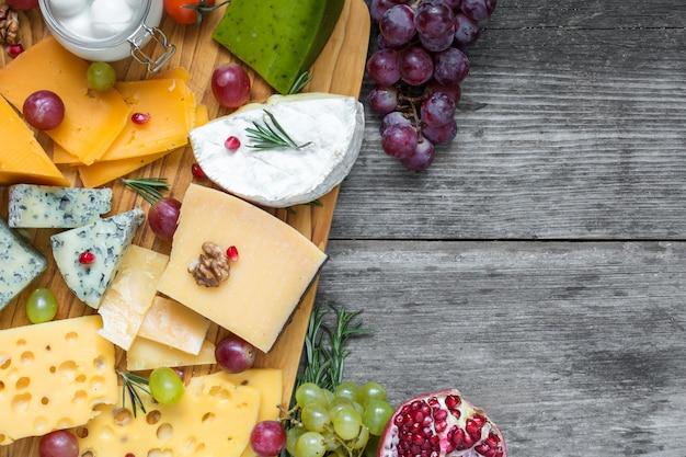 Verschiedene käsesorten auf holzplatte mit walnüssen, trauben, granatapfel und rosmarin
