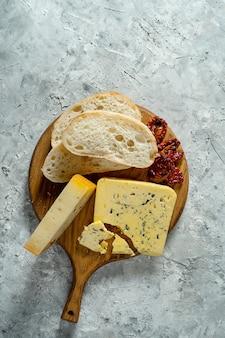 Verschiedene käsesorten auf holzschneidebrett. blauschimmelkäse mit ciabatta und sonnengetrockneten tomaten auf grauem hintergrund. abendessen mit italienischer küche. speicherplatz kopieren. weichzeichner, draufsicht
