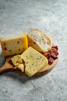 Verschiedene käsesorten auf holzschneidebrett. blauschimmelkäse mit ciabatta und sonnengetrockneten tomaten auf grauem hintergrund. abendessen mit italienischer küche. speicherplatz kopieren. weichzeichner, nahaufnahme