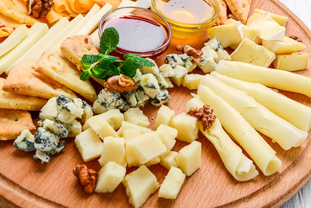 Verschiedene käsesorten auf schwarzem schiefer, nüssen und honig, dekoriert mit trauben und minzblättern