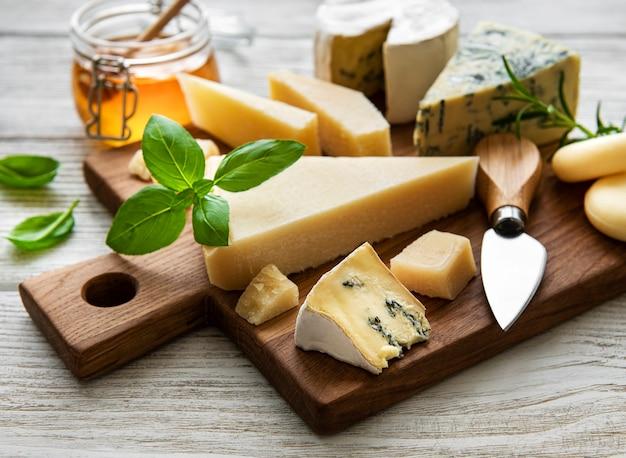 Verschiedene käsesorten auf weißer holzoberfläche