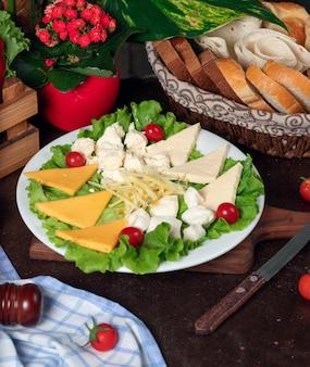 Verschiedene käsesorten befinden sich auf einem holzbrett und sind mit kirschtomaten, salat und frischem brot dekoriert.