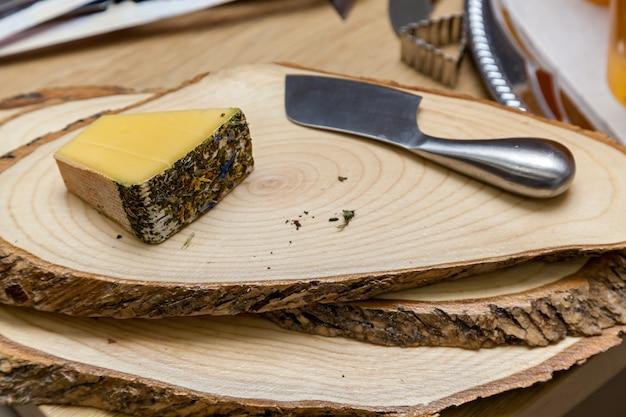 Verschiedene käsesorten bei einer präsentation von käseherstellern. draufsicht auf eine käseplatte mit blauschimmelkäse, brie mit nüssen, honig auf einem holztisch.
