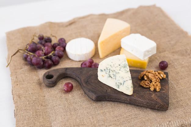 Verschiedene käsesorten, blauschimmelkäse und brie mit trauben und nüssen.