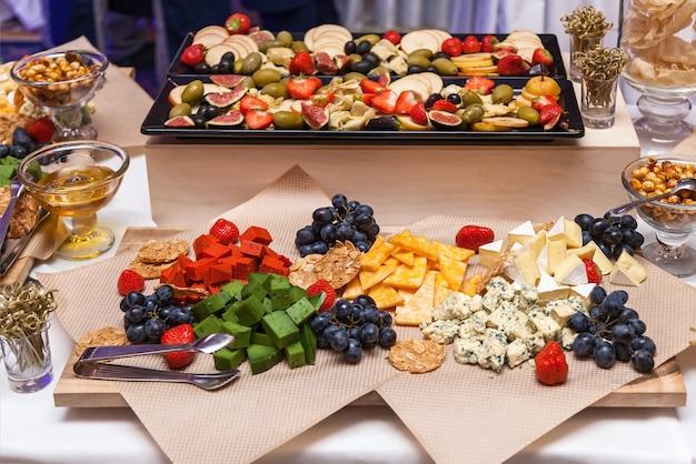 Verschiedene käsesorten, die in dreiecke geschnitten sind, liegen mit erdbeeren auf dem papier. verschiedene käsesorten