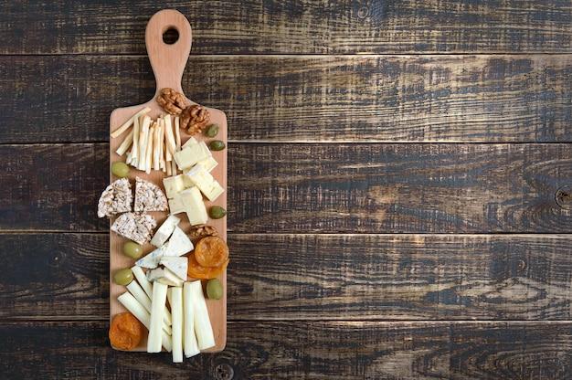 Verschiedene käsesorten, getrocknete aprikosen, vollkornbrot, nüsse, oliven, kapern auf einem holzbrett.