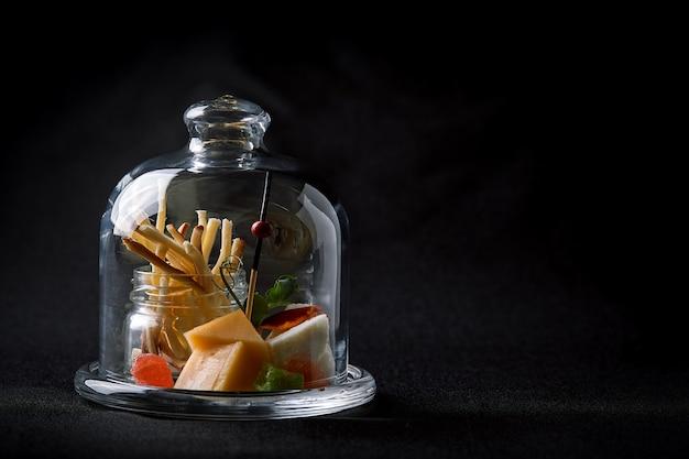 Verschiedene käsesorten mit beeren und marmelade, mini-aufschlag in einem glaskolben. fusionslebensmittelkonzept, zurückhaltend, kopienraum.
