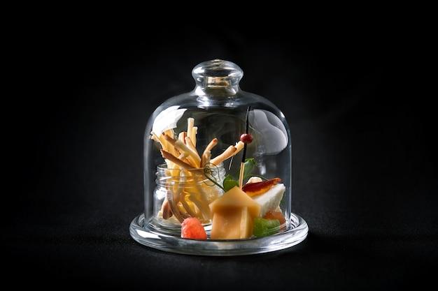 Verschiedene käsesorten mit beeren und marmelade, mini-aufschlag in einem glaskolben.