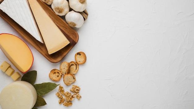 Verschiedene käsesorten mit brotscheibe; nussbaum; knoblauch und lorbeerblätter über weißem hintergrund