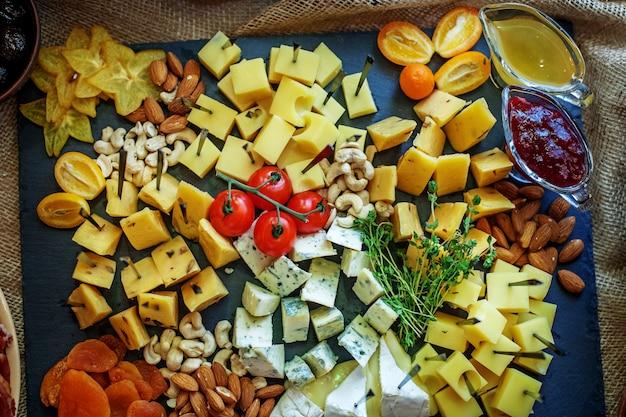 Verschiedene käsesorten mit früchten, saucen und nüssen.