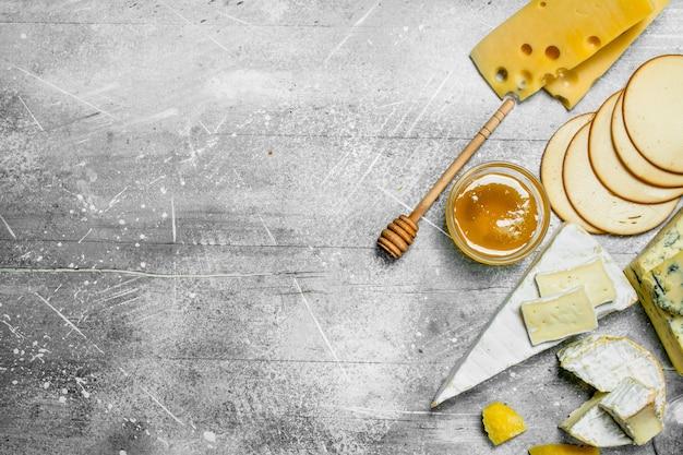 Verschiedene käsesorten mit honig. auf einem rustikalen.