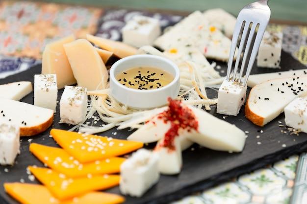 Verschiedene käsesorten mit honig schneiden