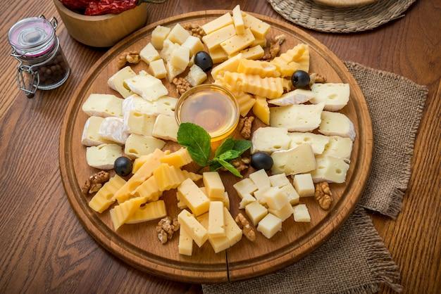 Verschiedene käsesorten mit honig und nüssen