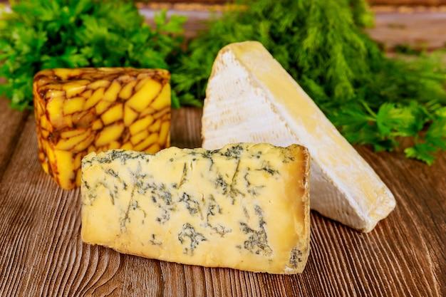 Verschiedene käsesorten mit kraut auf holzoberfläche