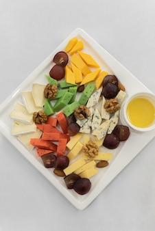 Verschiedene käsesorten mit nüssen auf einem weißen teller grauer hintergrund ansicht von oben
