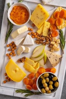 Verschiedene käsesorten mit nüssen, birnen, getrockneten aprikosen und rosmarin.