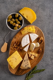 Verschiedene käsesorten mit nüssen, oliven und rosmarin.