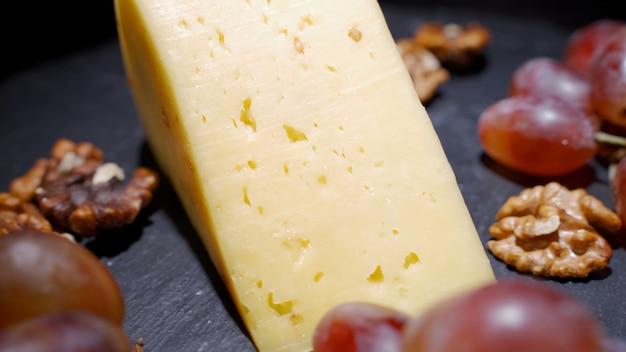 Verschiedene käsesorten mit nüssen und trockenfrüchten auf dem tisch