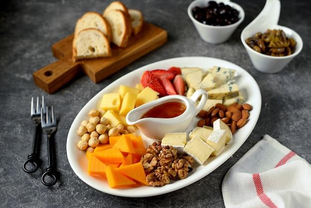 Verschiedene käsesorten mit oliven, nüssen, früchten und honig. vorspeise für eine weinparty.
