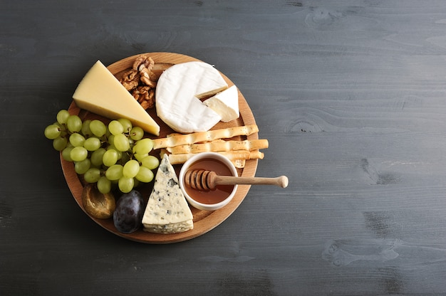 Verschiedene käsesorten mit schimmel, honigtrauben und nüssen