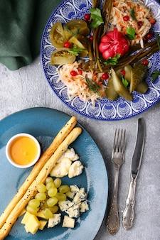 Verschiedene käsesorten mit trauben, honig und brot und teller mit verschiedenem eingelegtem gemüse draufsicht