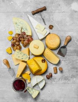 Verschiedene käsesorten mit trauben, nüssen und einem glas rotwein. auf einem rustikalen tisch.