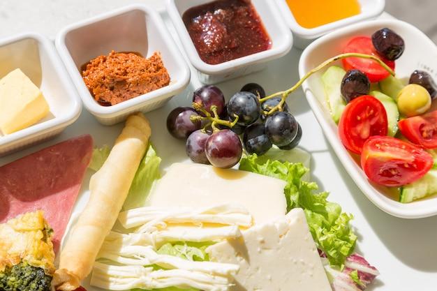 Verschiedene käsesorten mit trauben, tomaten, gurken und saucen.