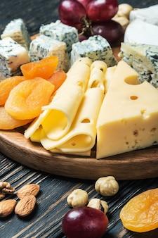 Verschiedene käsesorten mit trauben und nüssen