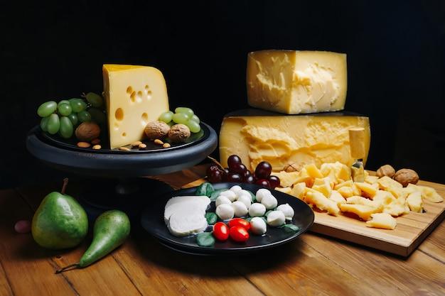 Verschiedene käsesorten mit walnüssen und trauben auf rustikalem holzhintergrund