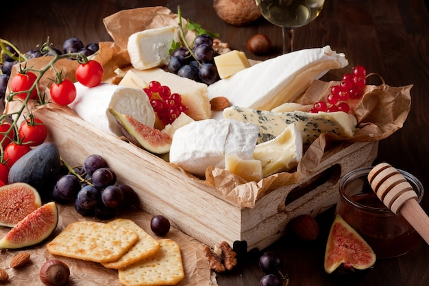 Verschiedene käsesorten mit wein, früchten und nüssen. camembert, ziegenkäse, roquefort, gorgonzolla, gauda, parmesan, emmentaler, brie