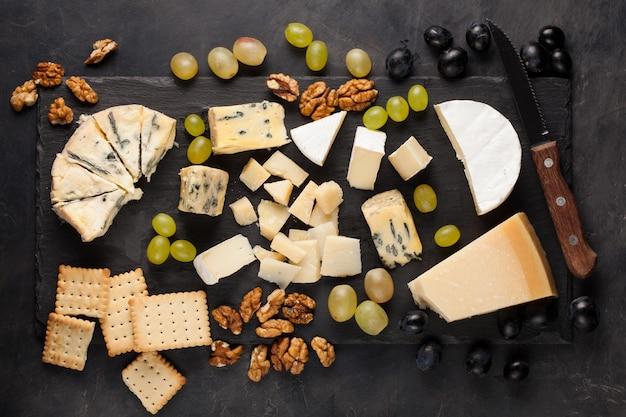 Verschiedene käsesorten mit weißen trauben.