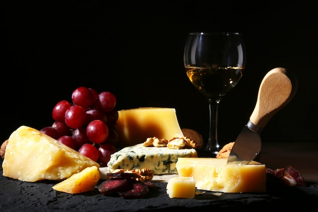 Verschiedene käsesorten, nüsse, trauben, geräuchertes fleisch und ein glas wein.