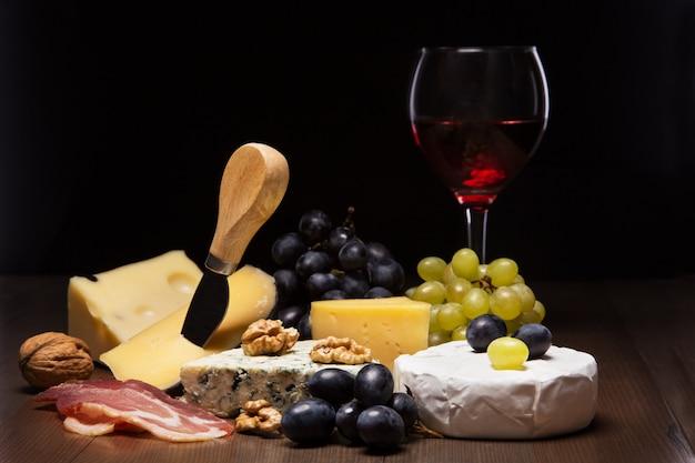Verschiedene käsesorten, nüsse, trauben, obst, geräuchertes fleisch und ein glas wein auf einem serviertisch. dunkler und launischer stil.