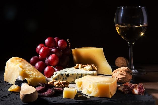 Verschiedene käsesorten, nüsse, trauben, obst, geräuchertes fleisch und ein glas wein auf einem serviertisch.