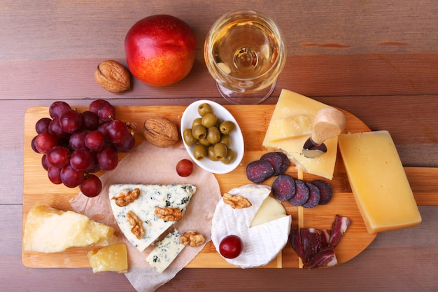 Verschiedene käsesorten, nüsse, trauben, obst, geräuchertes fleisch und ein glas wein auf einem serviertisch