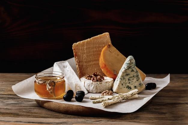 Verschiedene käsesorten. scheiben käse brie oder camembert mit parmesan, cheddar, blauschimmelkäse und andere mit nuss und honig auf holzbrett auf dunklem hintergrund