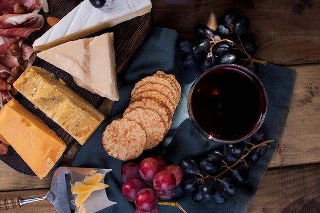 Verschiedene käsesorten, schinken, wein und trauben