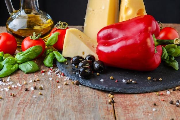 Verschiedene käsesorten, tomaten, paprika und olivenöl auf dunklem untergrund