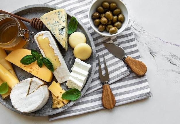 Verschiedene käsesorten, trauben, honig und snacks auf einem marmortisch
