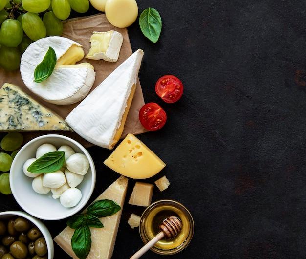 Verschiedene käsesorten, trauben, honig und snacks auf schwarzer betonoberfläche