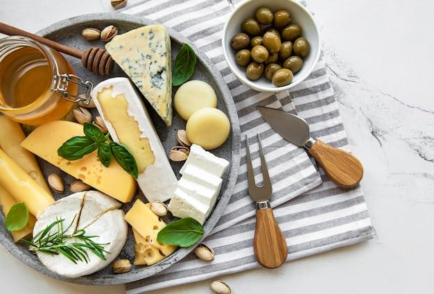 Verschiedene käsesorten, trauben, honig und snacks