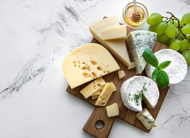 Verschiedene käsesorten, trauben und honig auf marmor