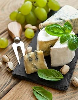 Verschiedene käsesorten, trauben und nüsse