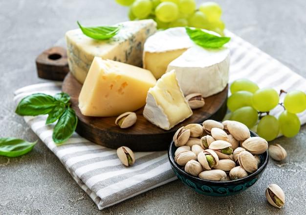 Verschiedene käsesorten, trauben und snacks auf einem grauen betontisch
