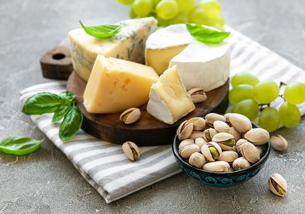 Verschiedene käsesorten, trauben und snacks